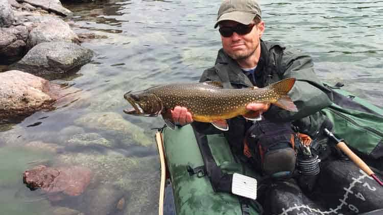 Fly fisherman on a fishing float tube with his catch, large trout fish (Brook Trout hybrid with Lake Trout, called Splake)