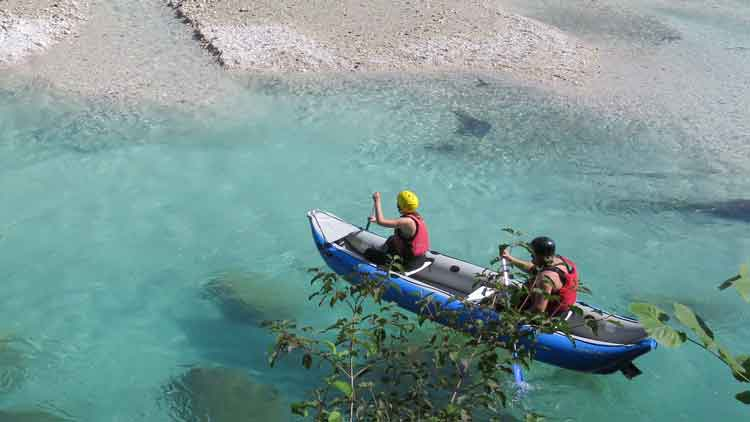 Two paddlers in a 2-person inflatable kayak on a beautifully clear river.
