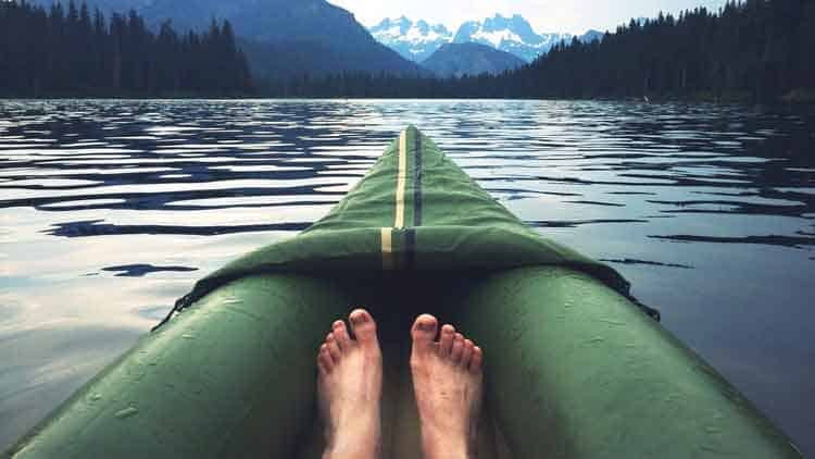 Paddler relaxing in an inflatable kayak on a large lake with mountains in the distance.