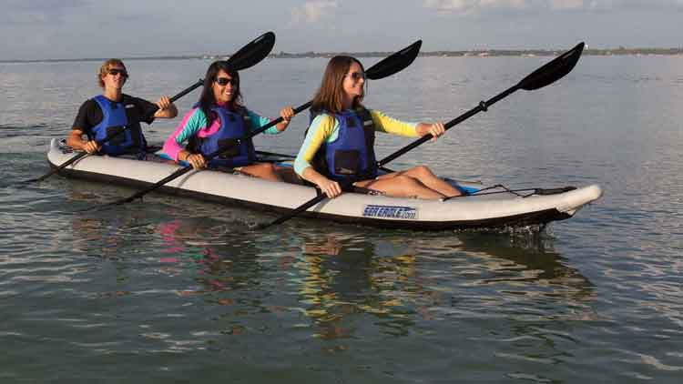 Three people in a Sea Eagle 465ft FastTrack inflatable kayak paddling in a bay.