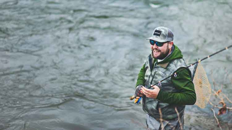 Fly fisherman in a great mood smiling along side a slow moving river.