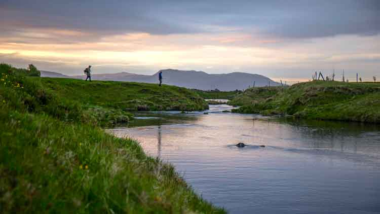 Two men beginning a day of fly fishing at a little river.
