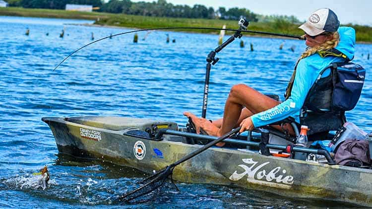 Female kayaker on a lake shooting video with a GoPro on a mount while catching a fish.