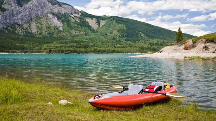 Inflatable kayak with inflatable seats on the shore of a lake at the base of a mountain.