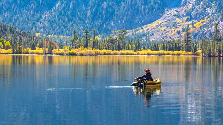 Fisherman in a fishing float tube on a calm lake in the mountains on a Fall day.