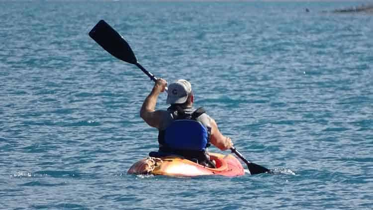 A man with high-angle paddling style with improperly set kayak paddle drip rings kayaking on open water.