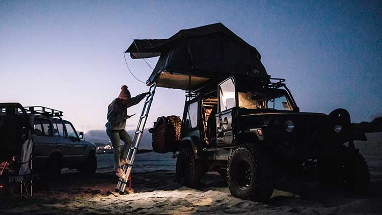 Night scene of a camper climbing down a ladder for accessing a Thule Tepui roof-top tent mounted on a Jeep Wrangler.