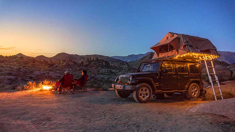 A couple sitting in camping chairs next to a Jeep Wrangler Sahara with a roof-top tent set up at a campsite in the desert at sunset.