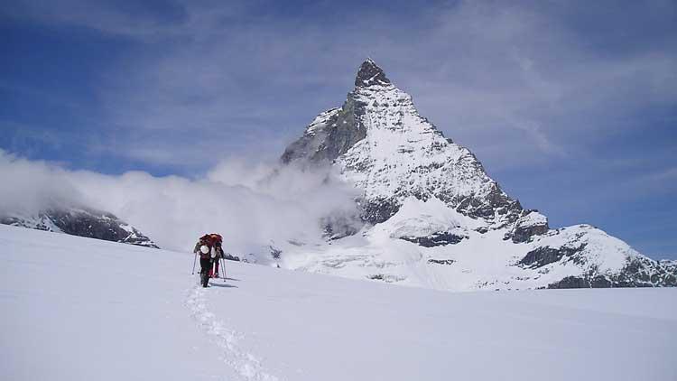 People snowshoeing on a trail below the Matterhorn.