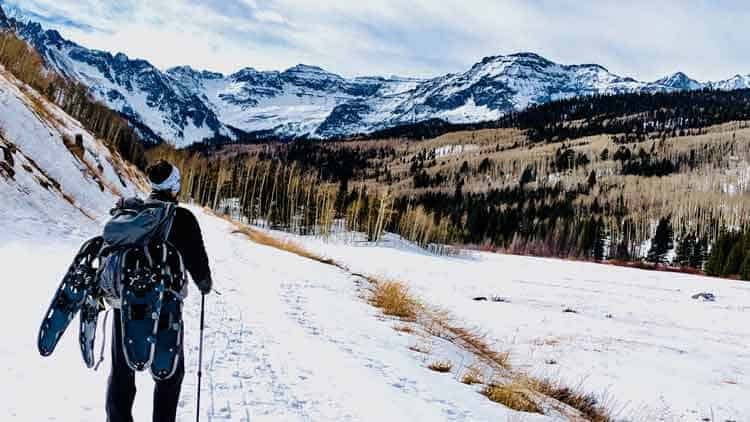 Man with snowshoes on a trail in the backcountry.