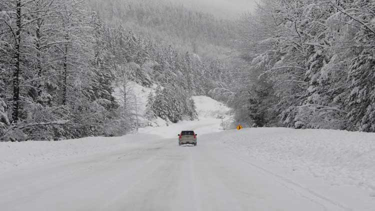 Snow covered road in the mountains make for treacherous conditions on the way to go snowshoeing.