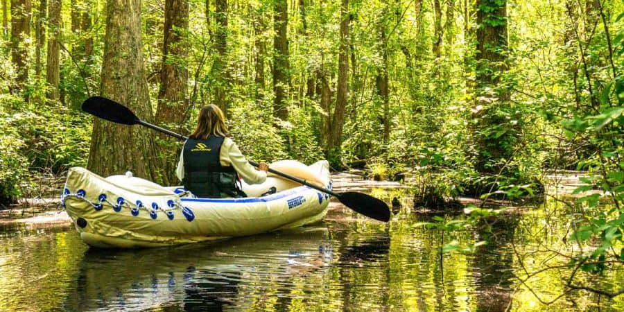 Female kayaker kayaking in an inflatable kayak through a beautiful swamp.