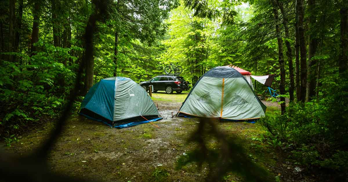 Campsite with two tents and an SUV with a mountain bike mounted on top. The large items brought to camp have been secured and small personal items stored away in the vehicle for protection.