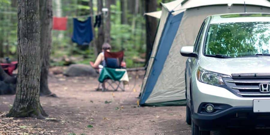 Campsite setup with car, tent, and camping chairs that is vulnerable to thieves.