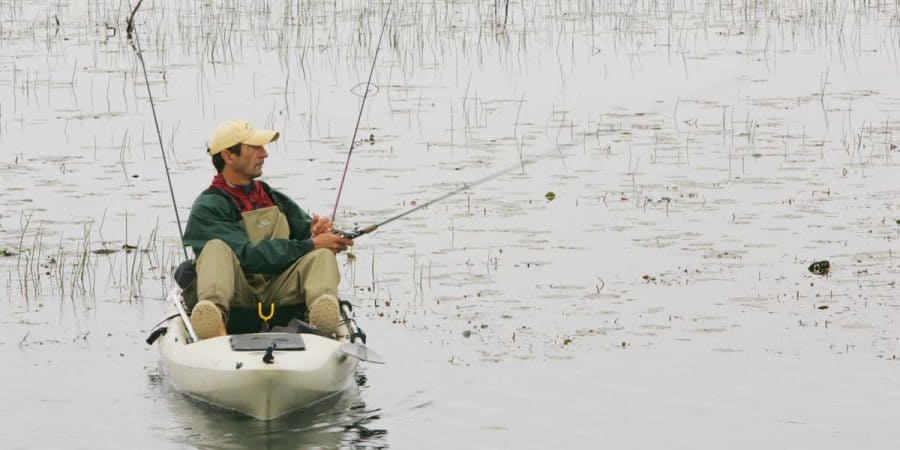 Man kayak fishing on a marshy lake.