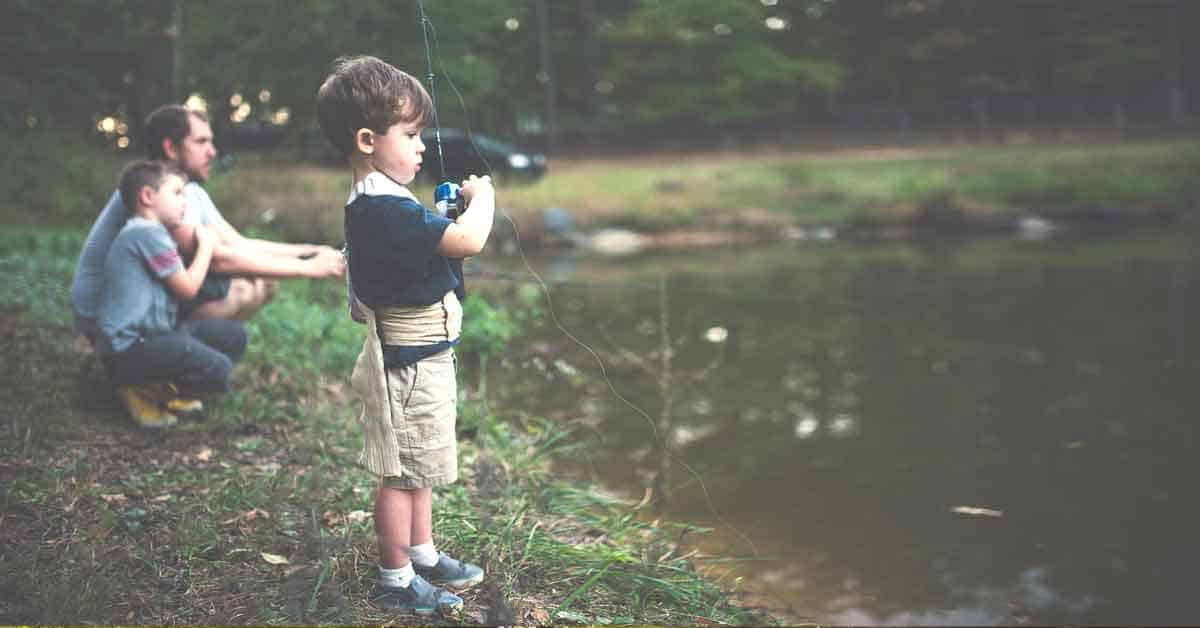 Father and two young boys fishing at the edge of a little pond.