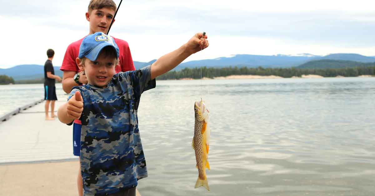 Three boys fishing from a dock. The youngest holds up his first catch.