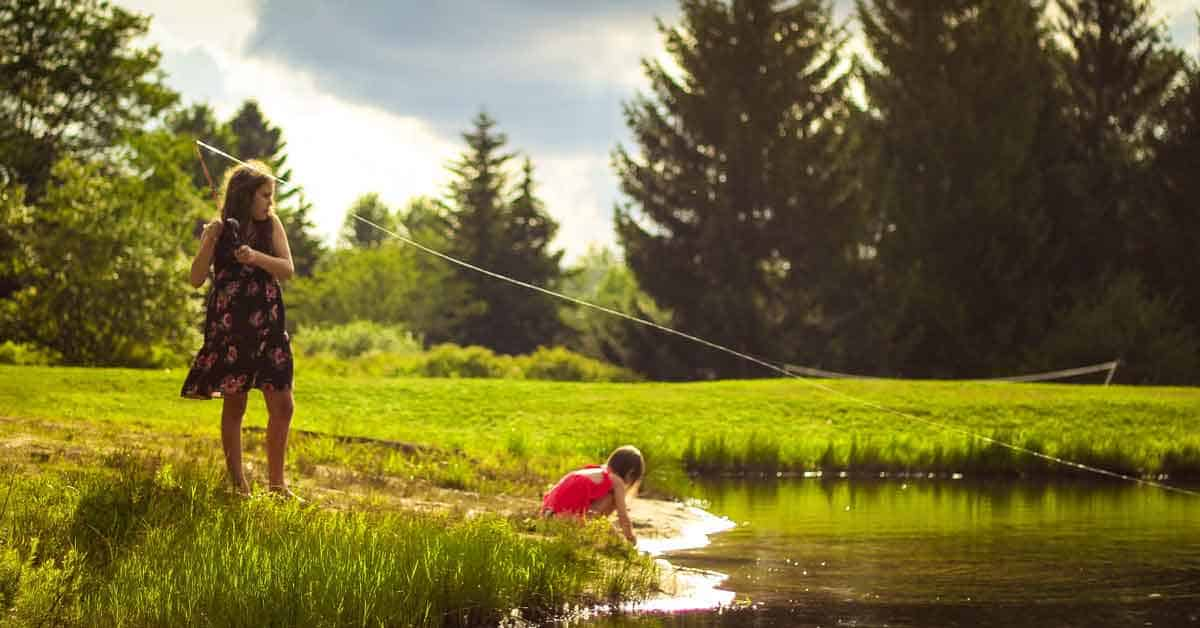 Two girls at a lake. The older girl fishes while the younger one explores at the water's edge.