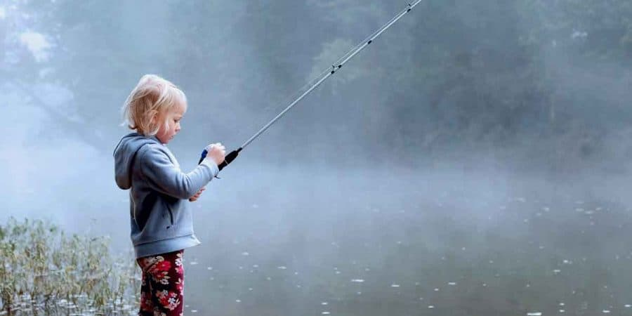 A little girl learning how to fish with a rod and reel combo at a lake on a foggy morning.