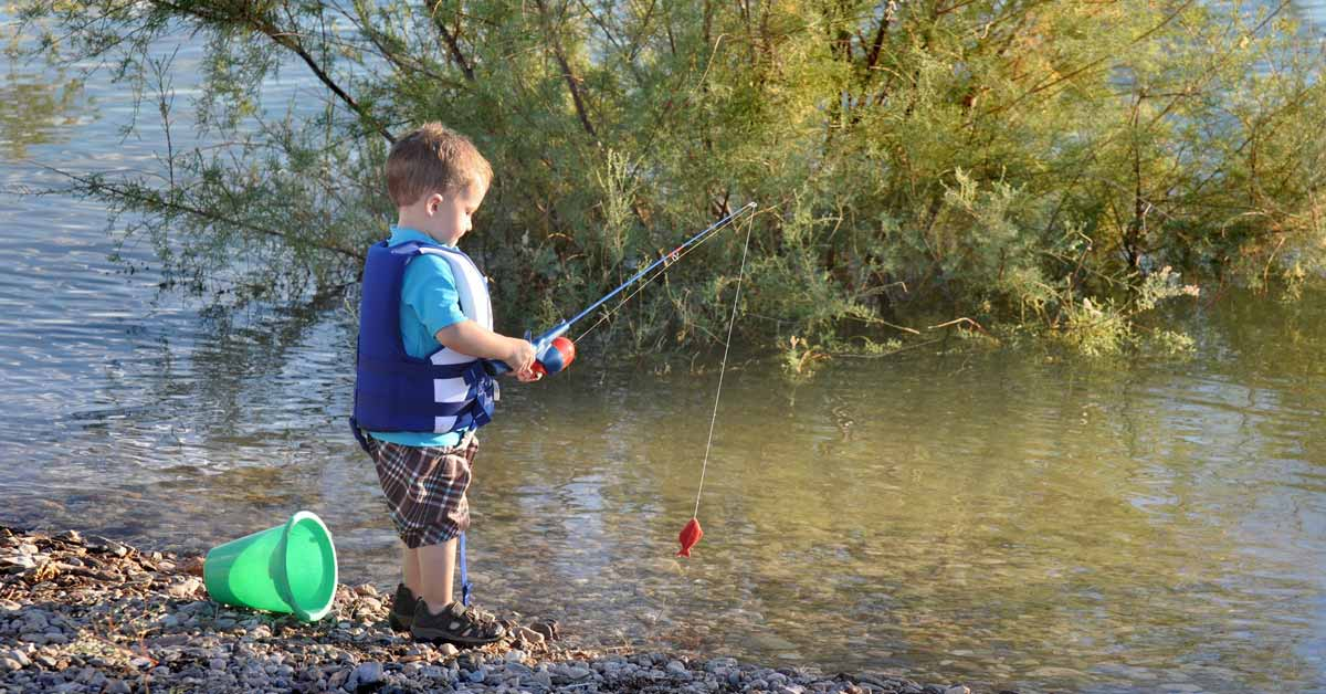 Toddler boy with a kid's rod and reel combo at the edge of a lake playing while learning how to fish.
