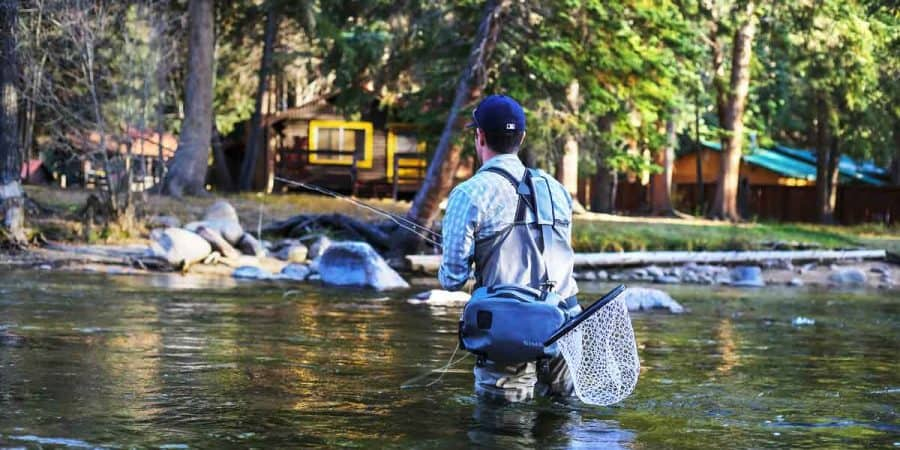 Fly fisherman wearing waders in a river while fishing.