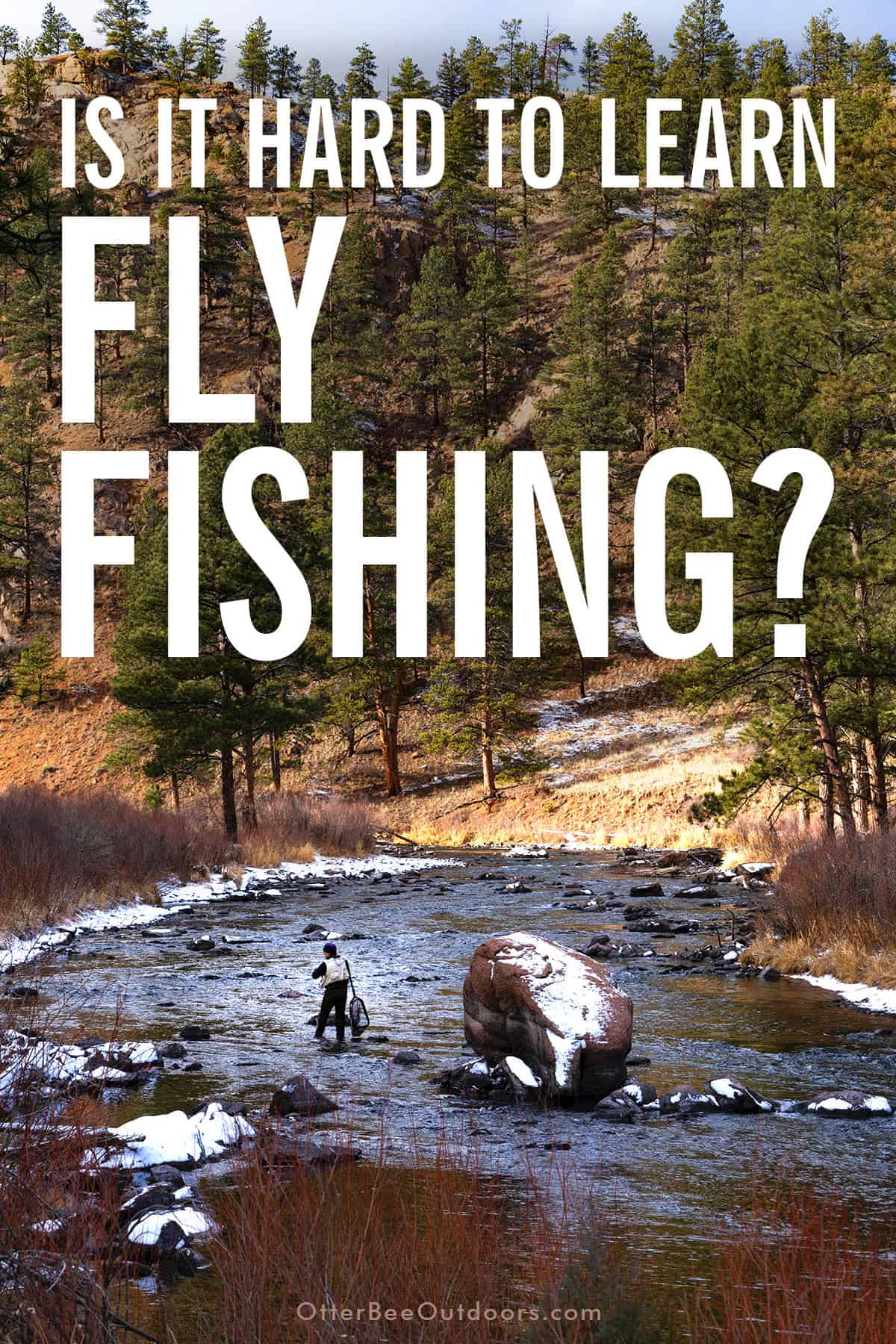 Fly fisherman in a cold mountain stream with patches of snow on the ground.
