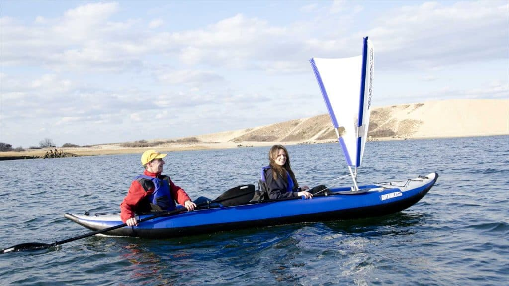 Two kayakers on a lake in a tandem Sea Eagle 420x Explorer inflatable kayak with a QuikSail Universal Kayak Sail.