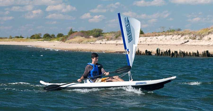 A man kayaking on a lake in a Sea Eagle 385ft FastTrack inflatable kayak with a Sea Eagle QuikSail Universal Kayak Sail Kit.