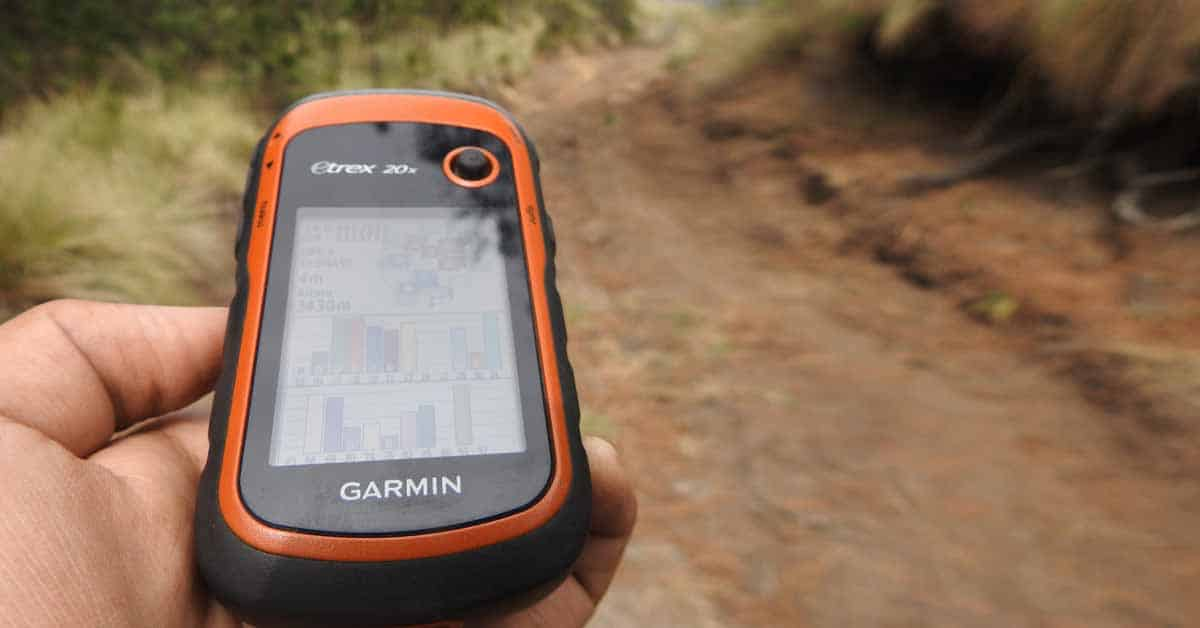 A hiker using a Garmin eTrex GPS device on a hiking trail.
