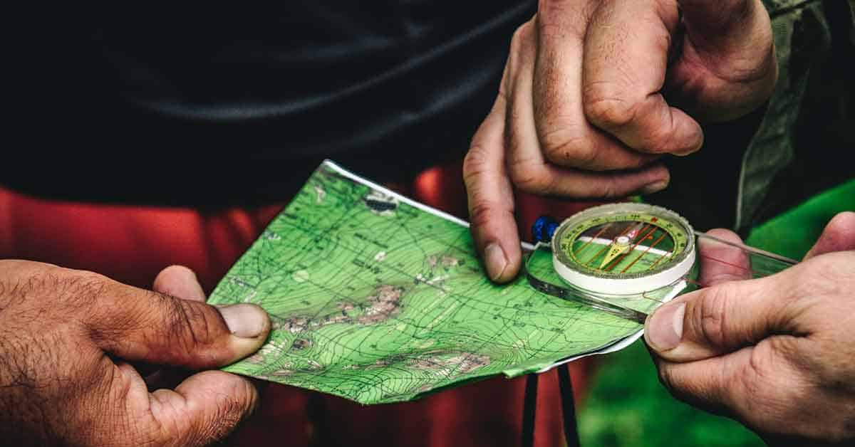 Backpackers using navigation tools (a map and compass) to find the hiking trail.