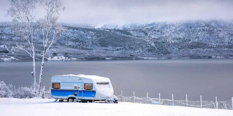 Camper set up at a lake on a snowy winter day.