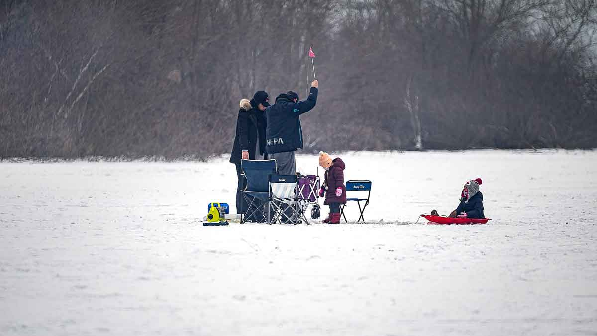 A family of four (mom, dad, and two children) ice fishing.