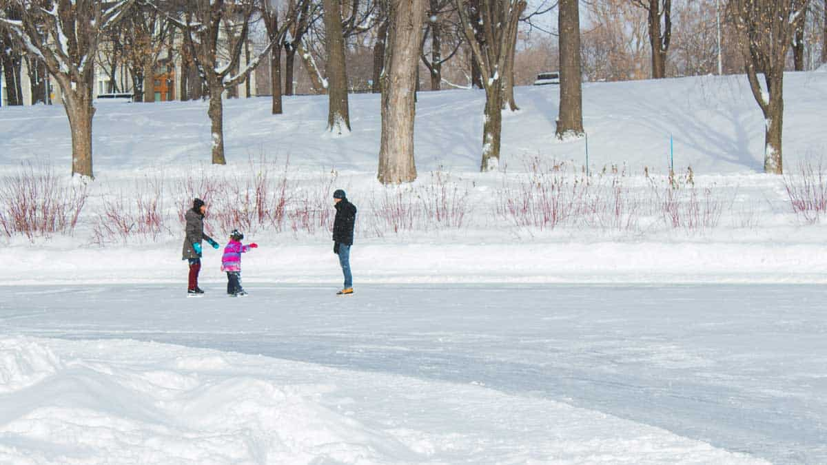 Mom, dad, and a little kid ice skating on a frozen lake.