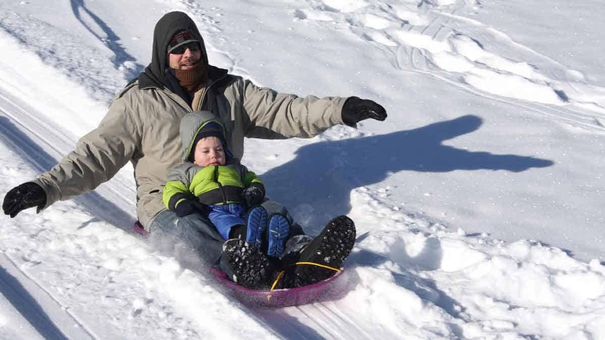 Father and son having fun sledding.