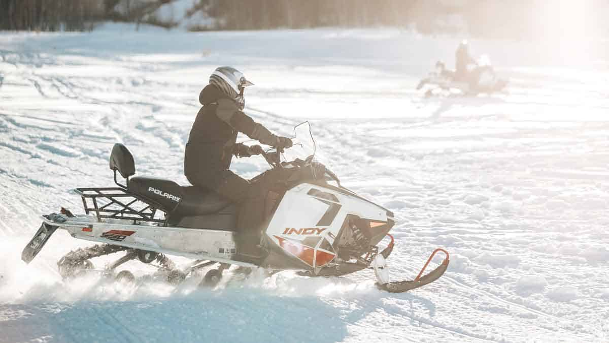 Having fun on snowmobiles in an open field.