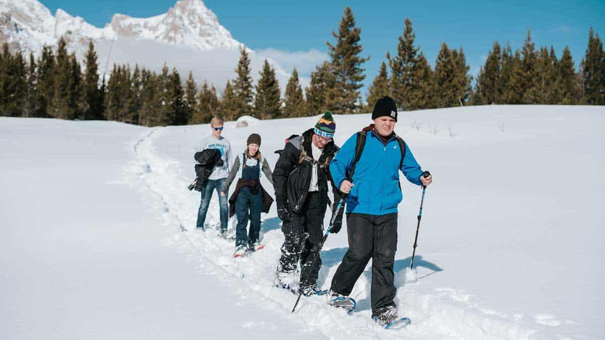 Four kids having fun snowshoeing along a snowy mountain trail.