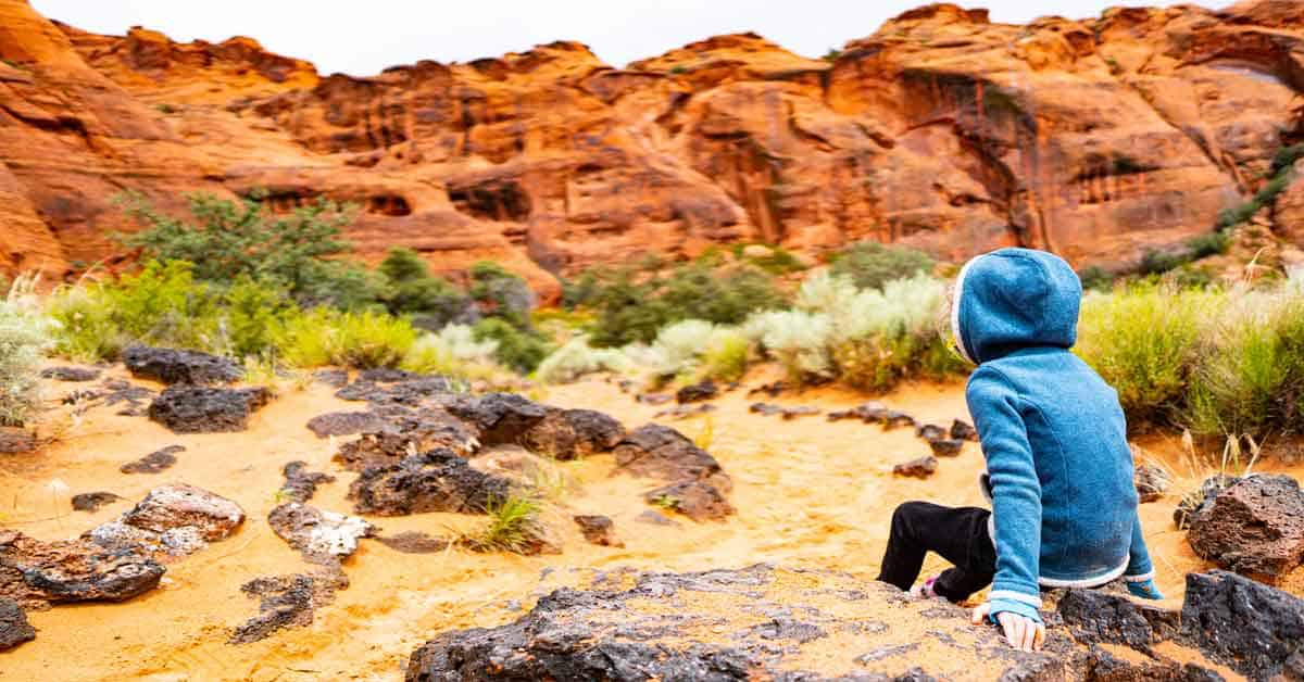 Child in a hooded jacket sitting on a rock while hiking in a arid region.