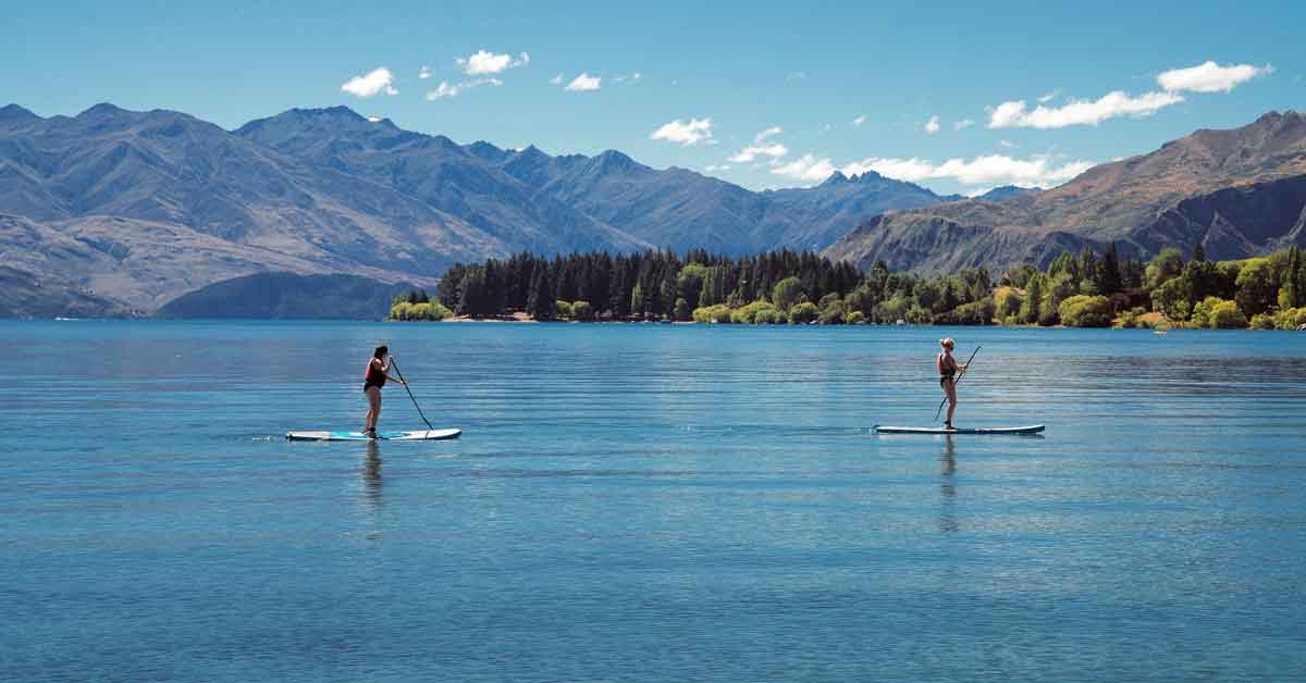 Two people paddle boarding on a mountain lake.