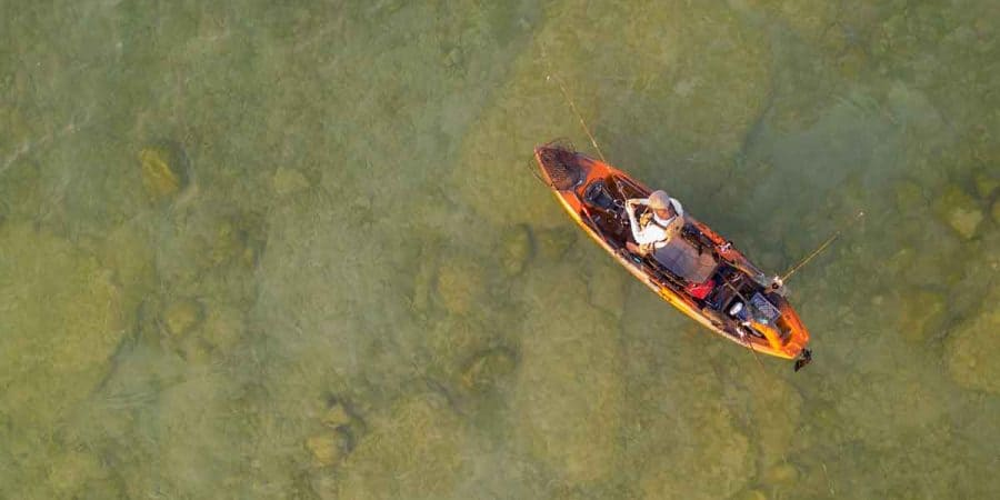 Fly fisherman in a fishing kayak in shallow water.