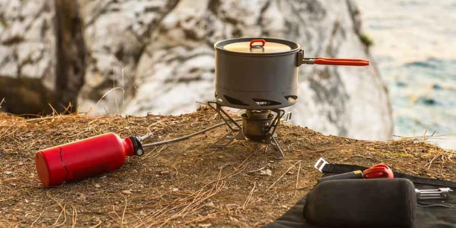 Liquid fuel (white gas) camping stove set up for cooking on a cliff overlooking the ocean in winter.