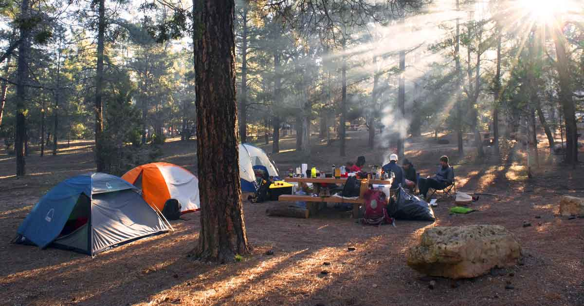 Campsite set up with three tents and a group of campers gathered around a fire near a picnic table.