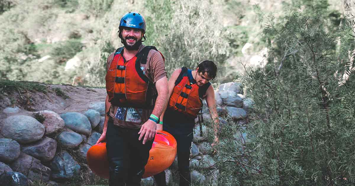 Two kayakers carry a kayak together.