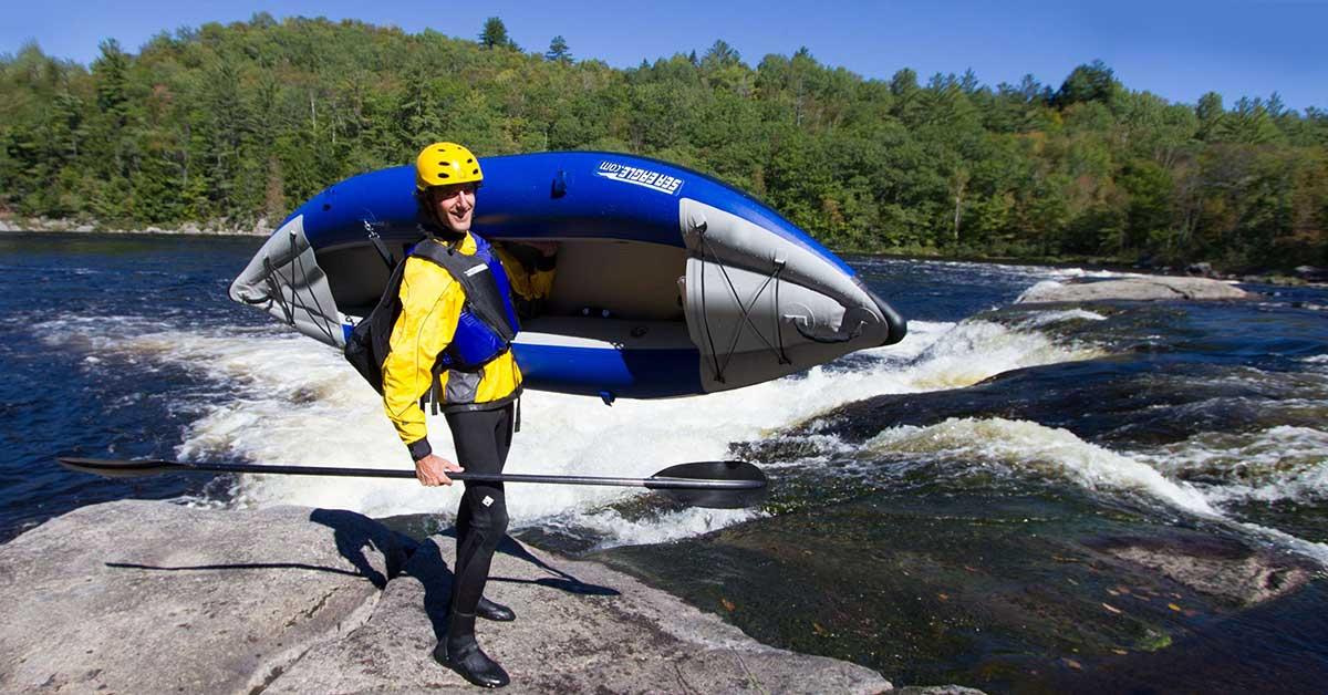 Portaging a Sea Eagle 300x Explorer inflatable kayak at a spot in the river with whitewater and rapids.