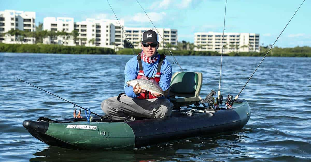 A fisherman showing of a prize catch in a Sea Eagle 350fx Fishing Explorer inflatable kayak.