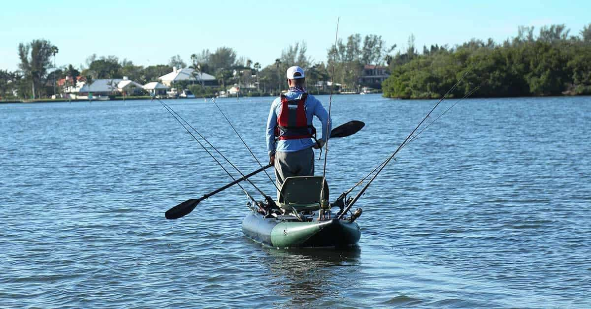 A fisherman standing up to paddle a Sea Eagle 350fx Fishing Explorer inflatable kayak.