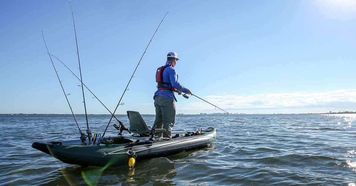 A fisherman standing up and fishing in a Sea Eagle 350fx Fishing Explorer inflatable kayak.