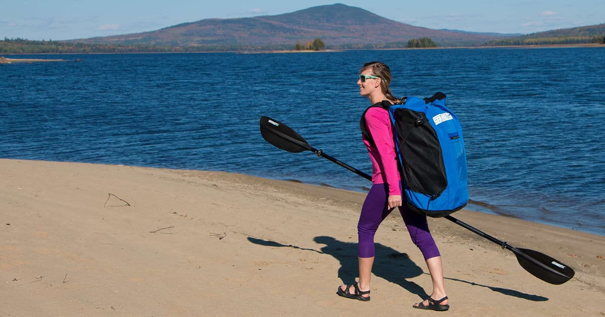 Female kayaker backpacking on a beach with a Sea Eagle 393rl RazorLite inflatable kayak.