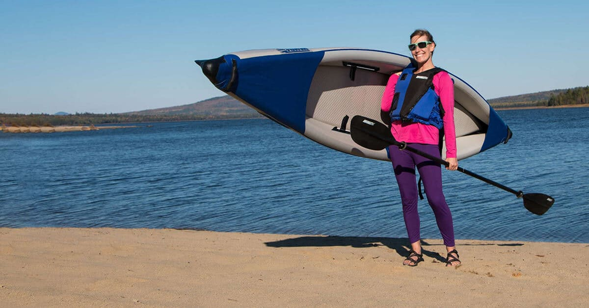 Female kayaker solo carrying a Sea Eagle 393rl RazorLite inflatable kayak.