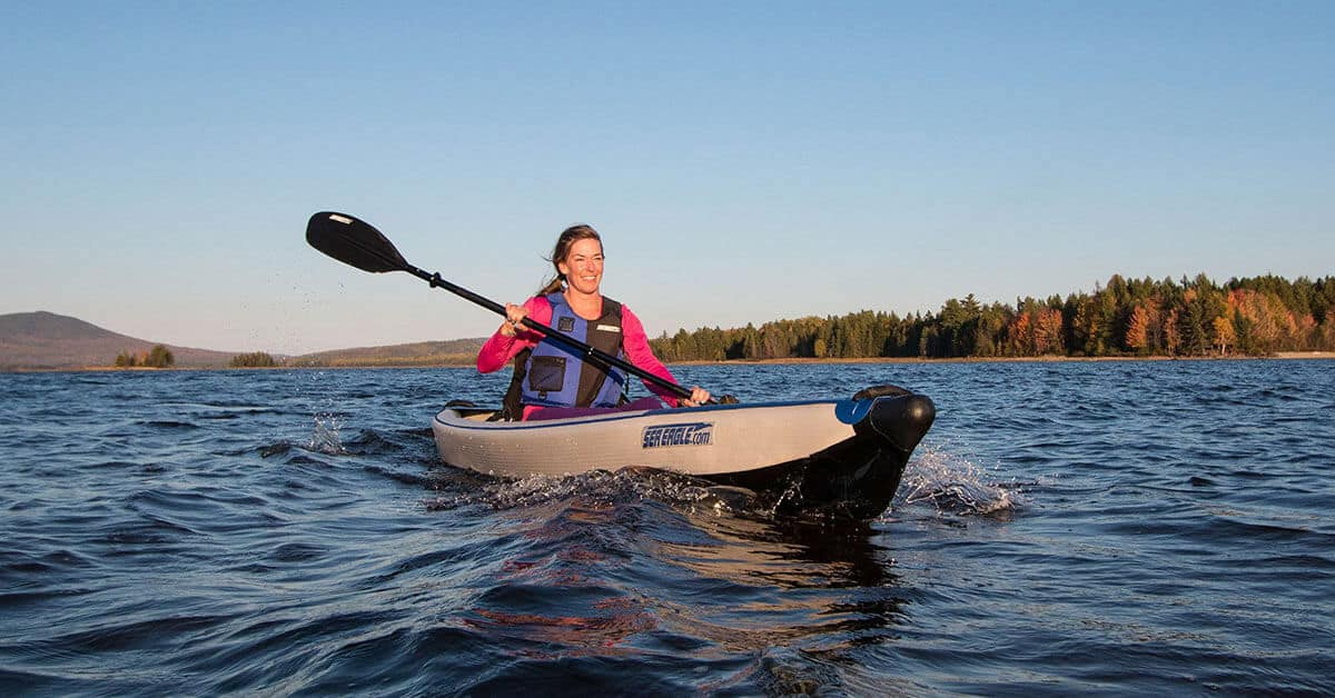 Female kayaker solo paddling a Sea Eagle 393rl RazorLite Inflatable Kayak on a flatwater lake.