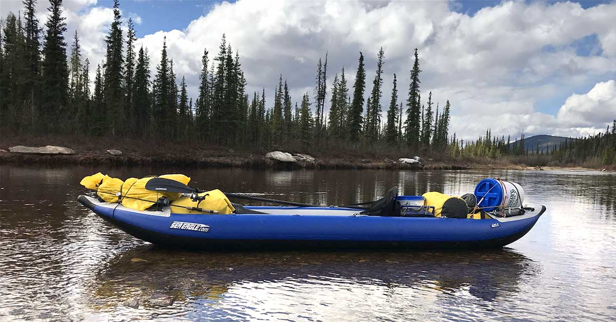 A Sea Eagle 420x Explorer inflatable kayak loaded down with gear fro camping and fishing.